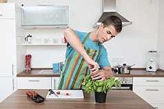 junger Mann zupft Basilikum