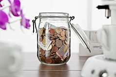 Offenes Glas mit Geld gefüllt in der Küche