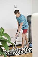 junger Mann saugt Zebrateppich