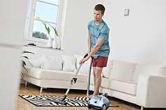junger Mann saugt Teppich