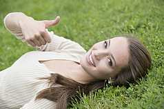 junge Frau liegt im Gras und gibt Handzeichen