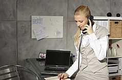 junge Businessfrau telefoniert und macht sich Notizen