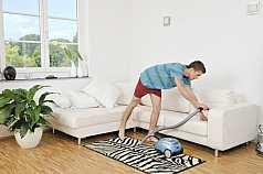 junger Mann saugt sein Sofa