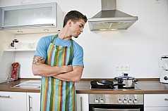 Mann schaut sich über die Schulter zu gekochtem
