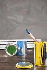 Pinsel in geöffneter Aluminiumfarbdose auf Holzuntergrund