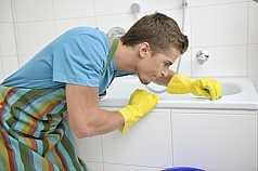 junger Mann putzt Badewanne