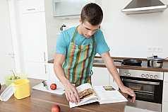 Mann kocht mit Kochbuch
