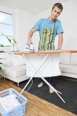 Mann bügelt im Wohnzimmer