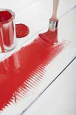 Lackierungsvorgang mit roter Farbe auf weißem Holz