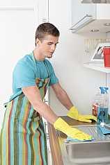 Mann putzt Küche