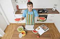 Mann in der Küche hält Wassermelone