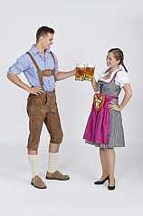 Junges Pärchen in Dirndl und Lederhose trinken Bier