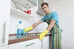 junger Mann putzt Spülbecken