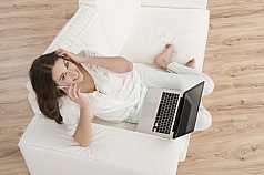 junge Frau mit Laptop sitzt telefonierend auf dem Sofa
