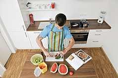 Mann schneidet Melone auf einem Brett