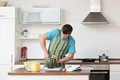 Mann zerteilt eine Wassermelone