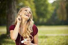 Frau sitzt im Park und hört Musik mit einem MP3 Player