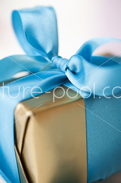 goldenes Paket mit blauer Schleife