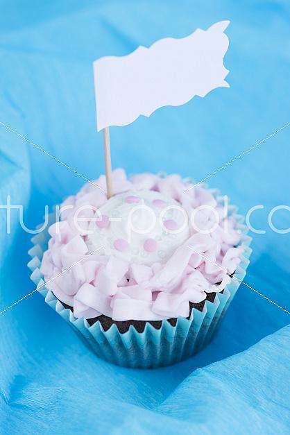Cupcake vor blauem Hintergrund und Fähnchen