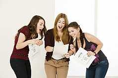 Drei Abiturientinnen mit Zeugnissen freuen sich