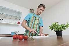 Mann schneidet Tomate