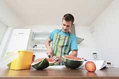 Mann zerkleinert eine Wassermelone