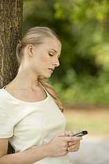 junge Frau liest SMS vom Handy