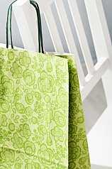 grüne Papiertüte hängt über Stuhllehne