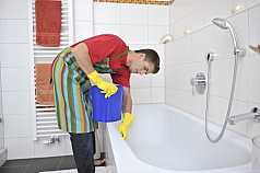 Mann wischt Badewanne