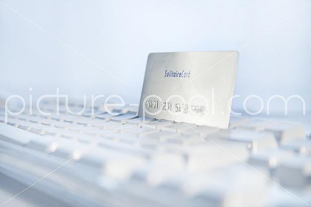 Kreditkarte steckt in Tastatur, Online-Shopping