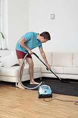 Mann saugt sein Wohnzimmer