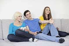 Drei Jugendliche mit Spielekonsole