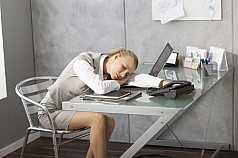 junge Frau ist erschöpft im Büro