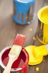 Farbeimer, Rot, Gelb, Blau mit Pinsel auf Holzboden