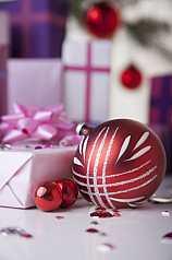 rote Christbaumkugeln vor Geschenken