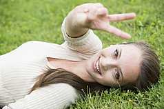 junge Frau macht Handgesten und liegt im Gras