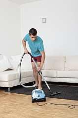 Mann saugt Teppich