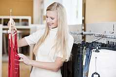 Junge blonde Frau beim Klamotten shoppen