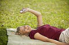junge Frau liegt auf der Wiese und hört Musik