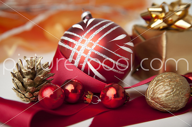 rote Christbaumkugeln mit goldenem Paket