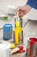 Hand mit Pinsel und bunten Farbeimern
