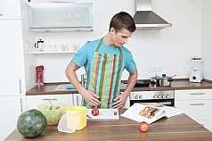 junger Mann in der Küche mit Kochbuch