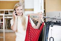 Junge blonde Frau beim shoppen und telefonieren