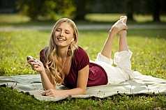 junge Frau liegt im Park und hört Musik mit einem MP3 Player
