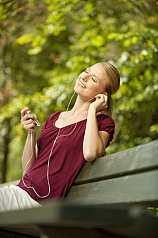 junge Frau sitzt auf Parkbank und hört Musik
