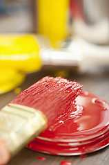 Pinsel mit roter Farbe auf Farbeimerdeckel