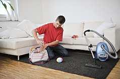 Mann räumt Kinderspielzeug weg