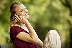 junge Frau sitzt auf Parkbank und telefoniert mit dem Handy