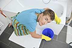 junger Mann putzt Badezimmer