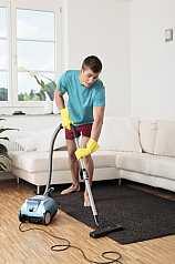 Junger Mann saugt Wohnzimmer
